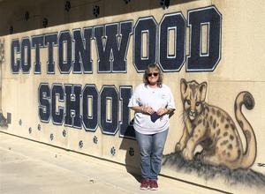 Claudia Taylor in front of a Cottonwood School sign.