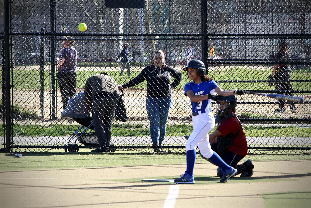 girl hitting a softball with a bat