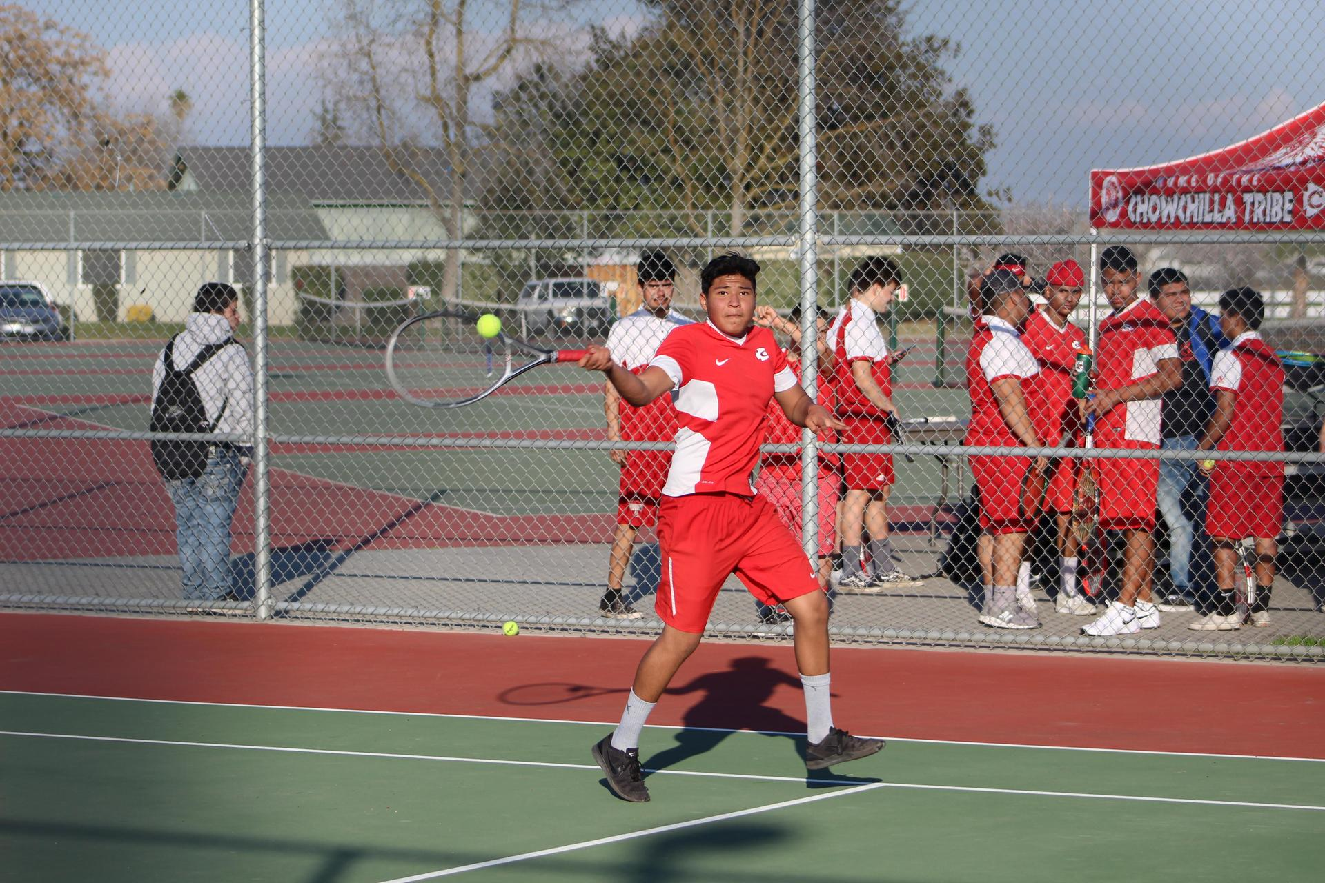 the tennis team watching a player through the fence