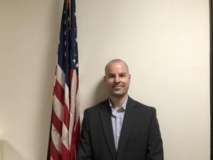 Photo of Nicolas Cammarano, our new IT Director wearing a blue shire and sport jacket standing next to the USA flag