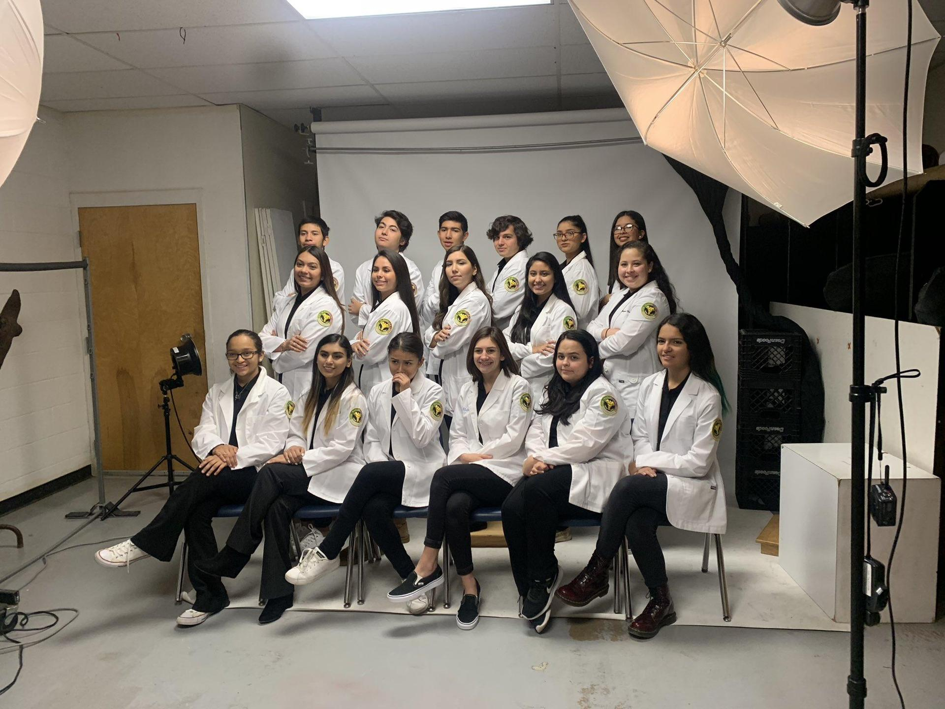 students in lab coats posing for picture