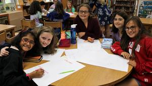 Photo of student members of Jefferson Early Act Club working on posters he created advertising the Wednesday Lunch service initiative.