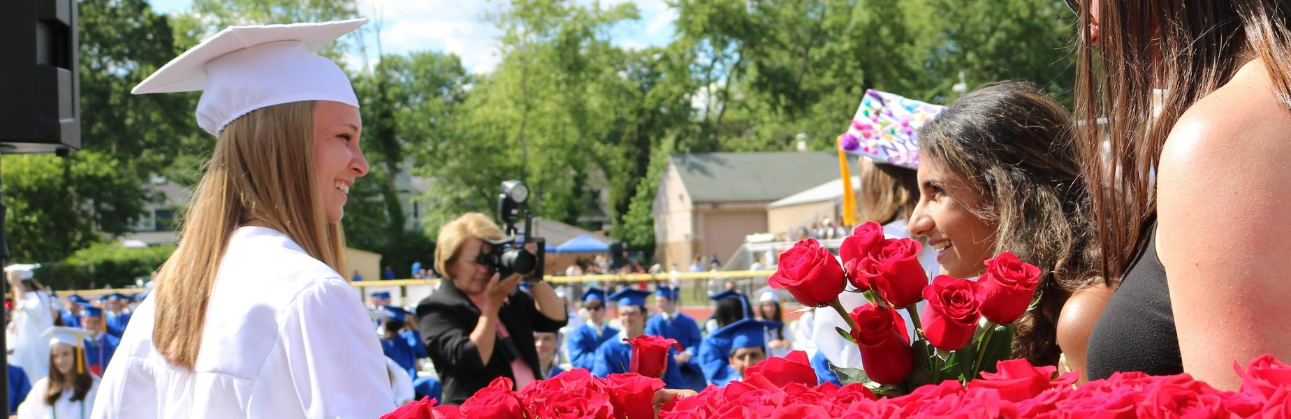 A Westfield High School graduate of the Class of 2021 accepts a rose and congratulations upon receiving her diploma.
