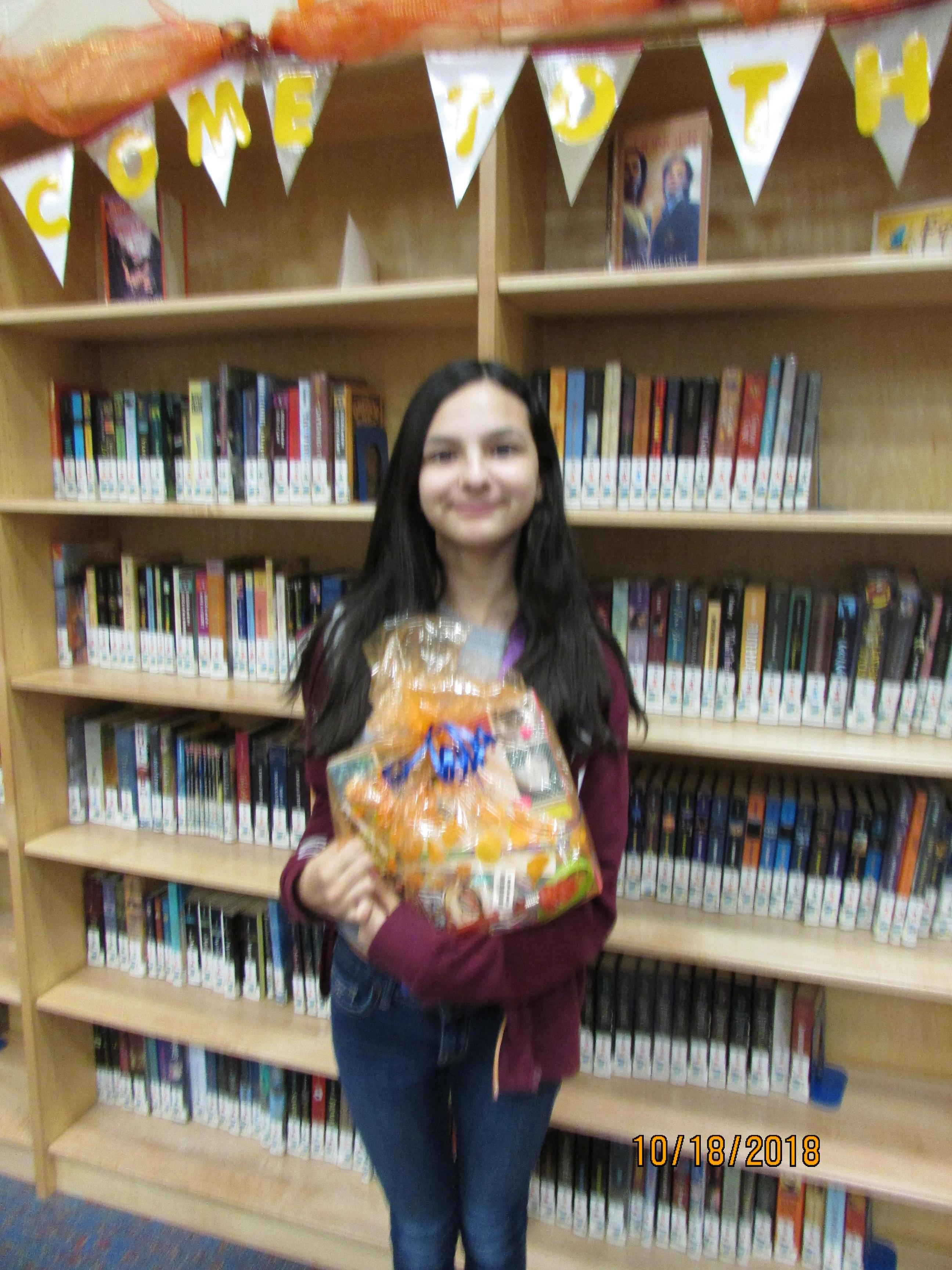 Photo of student holding prize for pumpkin decorating contest.