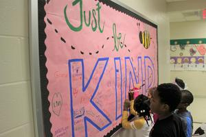 """Kindergartners at Batesburg-Leesville Primary School sign the """"Just Be Kind"""" bulletin board that is on display in the school Media Center.  The bulletin board, which was created specifically for Random Acts of Kindness Week, serves as a reminder for students to cultivate kindness and to go out of their way to brighten other people's day."""