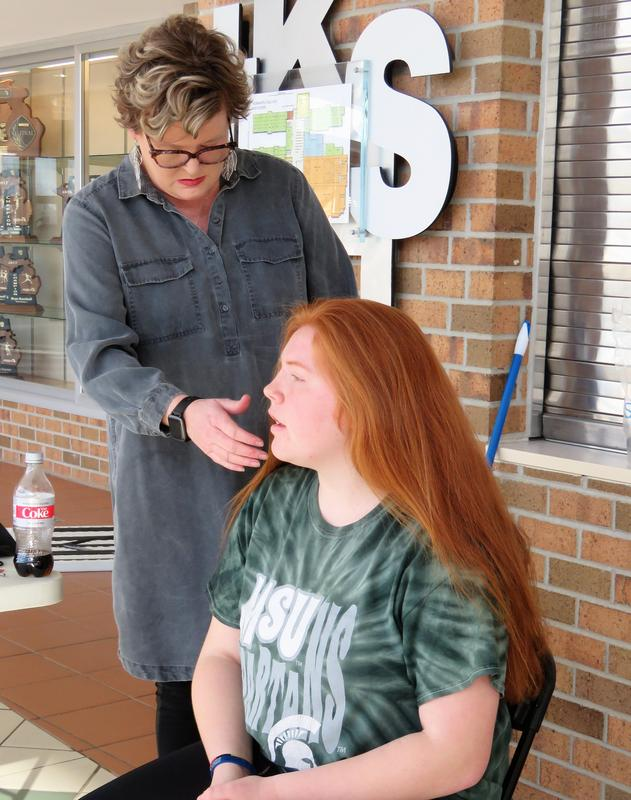 A TKHS student is ready to have her long, red hair cut and donated.