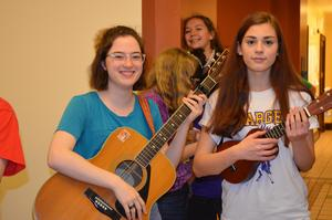 A photo of two students playing guitar and ukelele