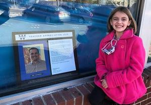 Abigail Drennan, a 5th grader at Jefferson Elementary School, praises teacher David Latessa for making virtual learning fun.  Abigail poses here with her winning submission at Baron's Drug Store in downtown Westfield.