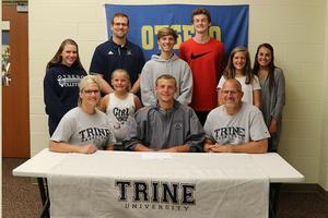 Zak Lucas, surrounded by family, his coach and friends before signing with Trine.