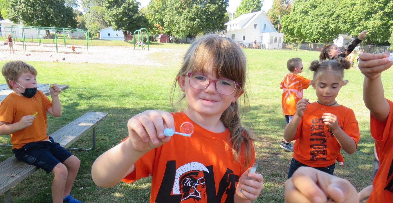 A student catches a bubble on her wand.
