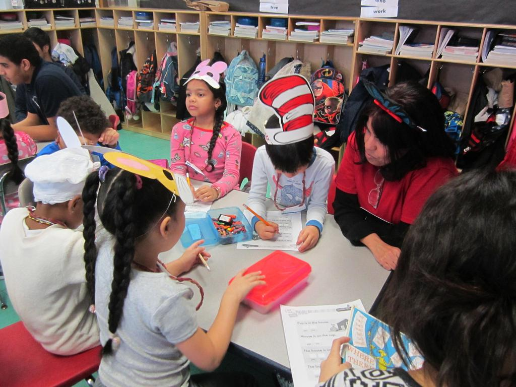 teacher working with a small group of children on an activity