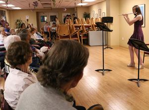 Photo of members of the WHS Band performing a volunteer concert at a senior citizens residence.