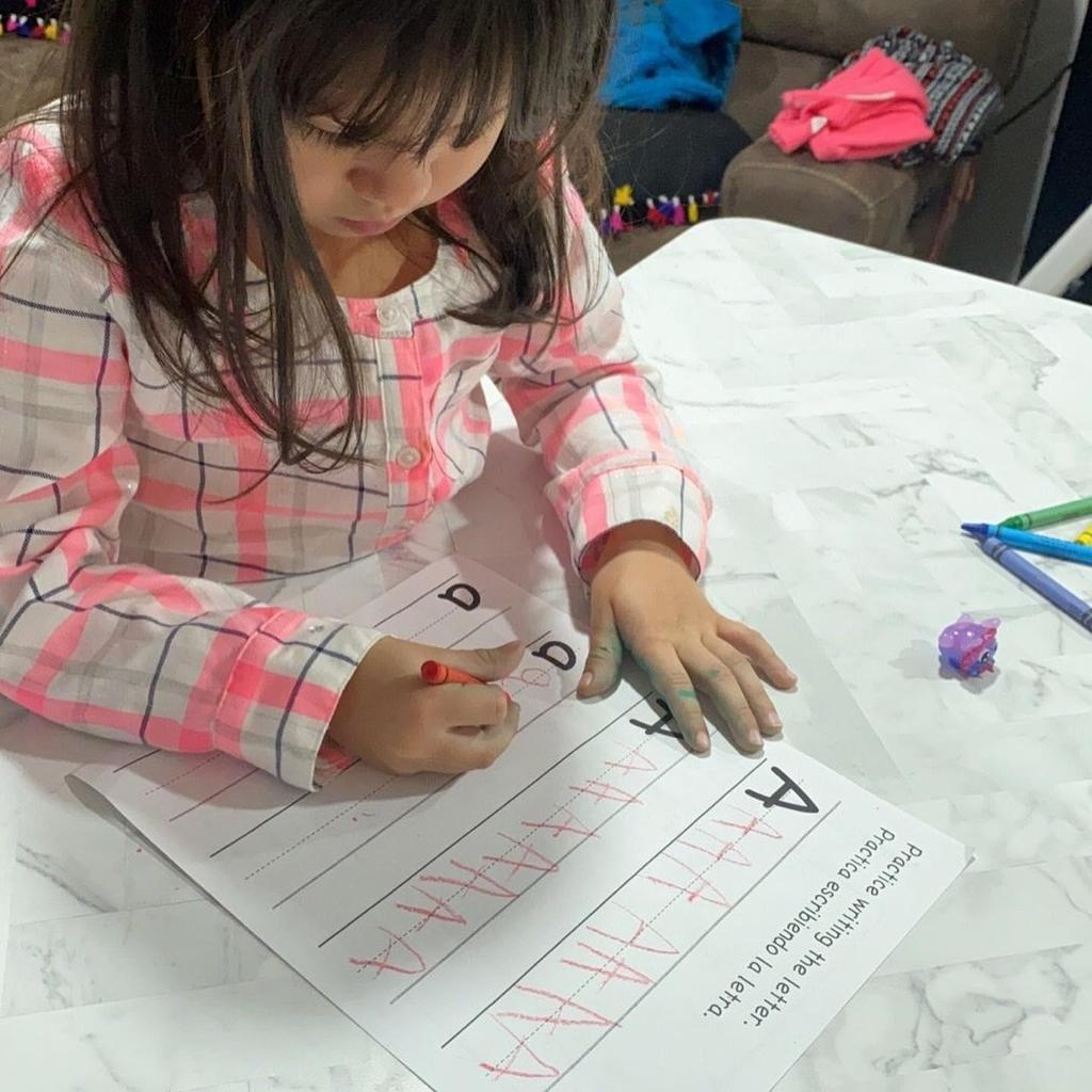little girl writing the letter A in red crayon