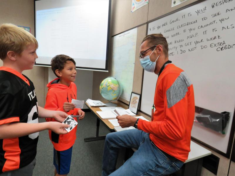 Two students try to barter with their teacher Mr. Wilkinson to trade their goods for gold or copper.