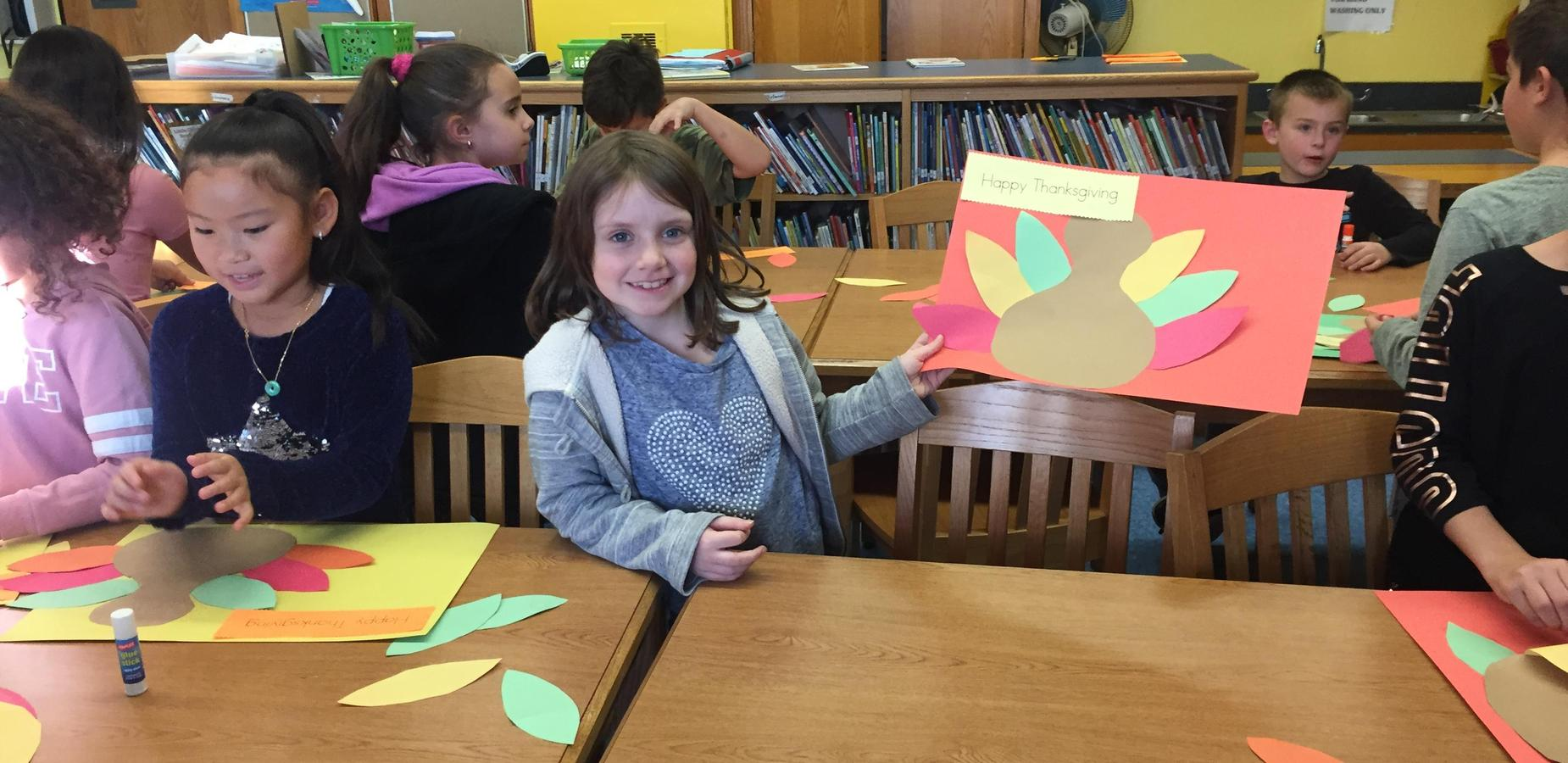 Student holding Thanksgiving placemat craft