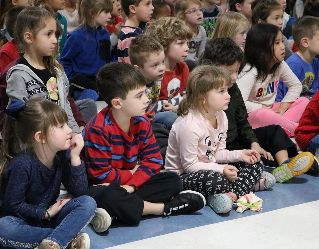Photo of Lincoln preschoolers and kindergartners enjoying a holiday concert by visiting 5th graders from Wilson School