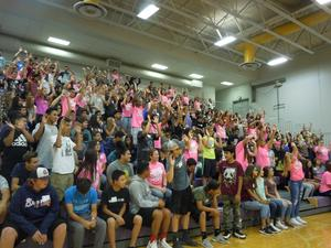 High school students in the stands have hands in the air.
