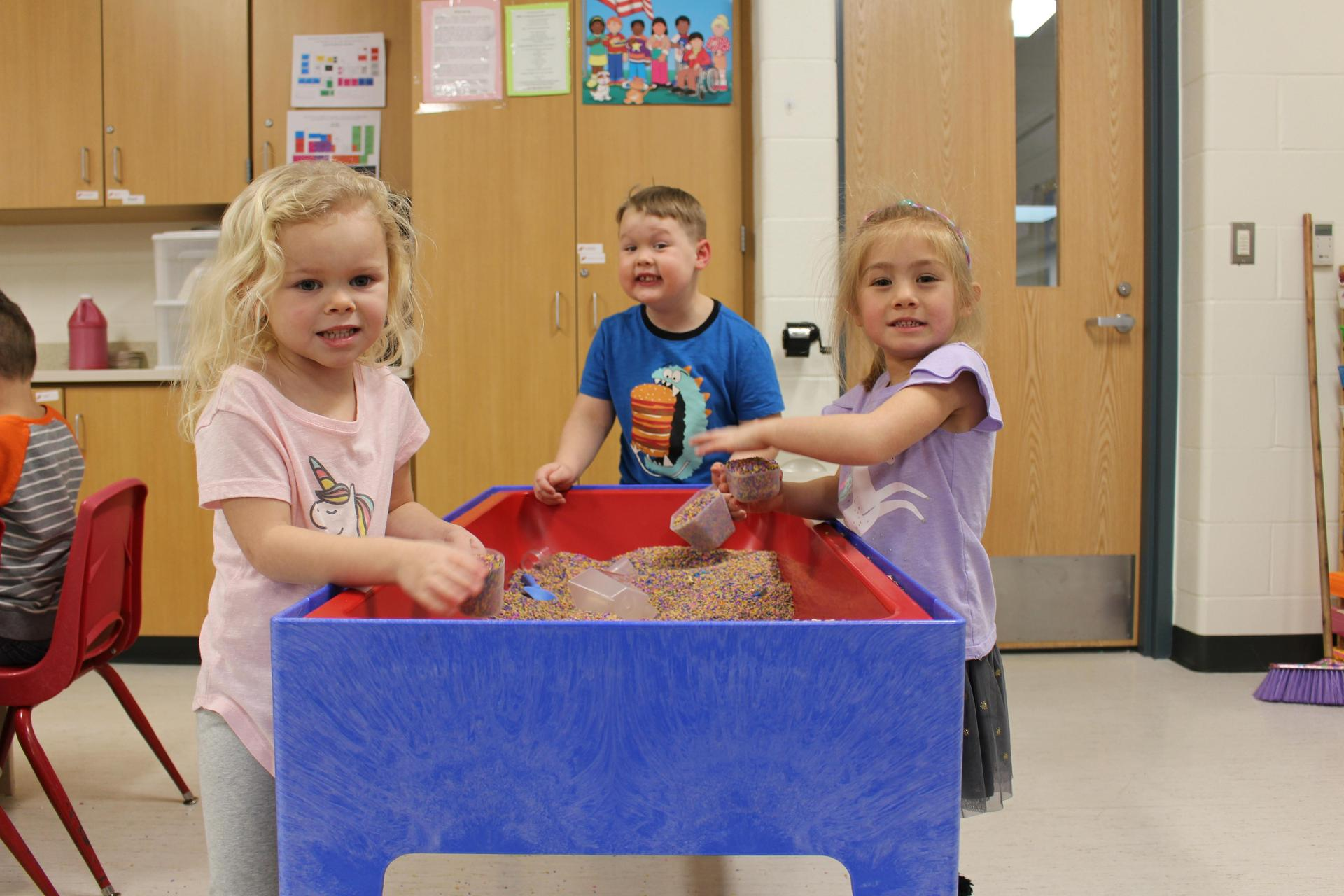 3 kids at sand table