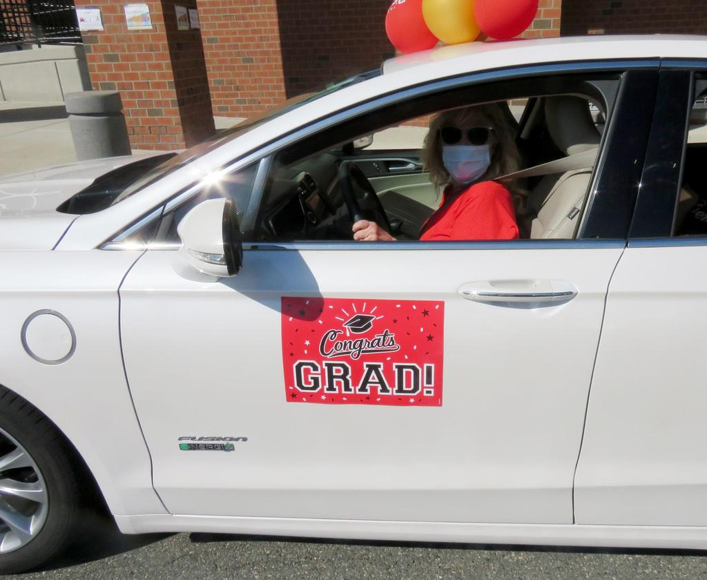 "A red ""Congrats Grad"" sign on a white car"