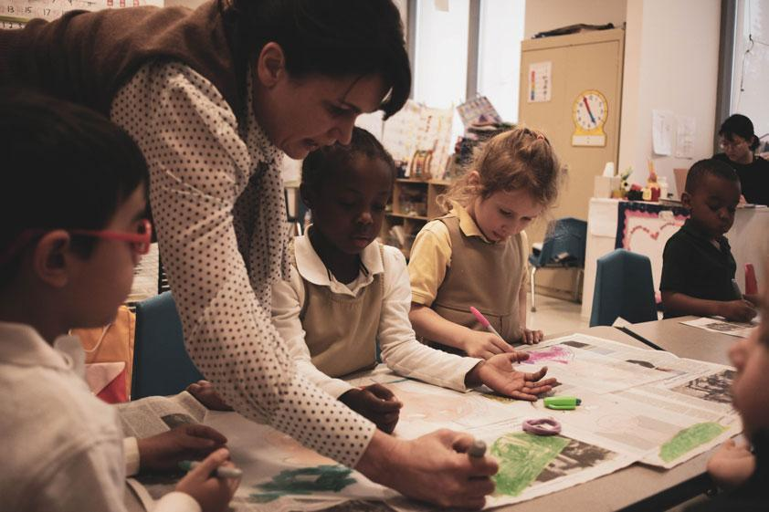 Teacher assists students in a self portrait project at HudsonWay Immersion School