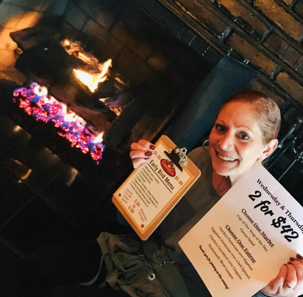 woman holding menus in front of a fireplace
