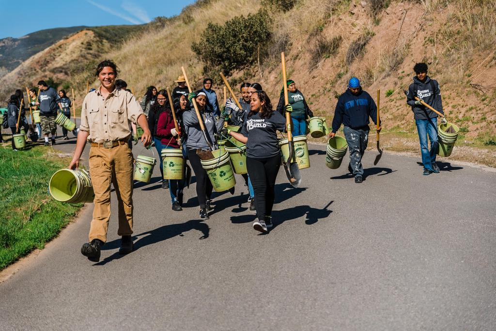 Lennox students carry tree planting supplies down a hill