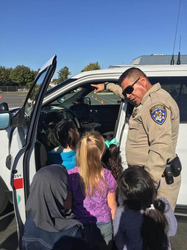 students lined up to look inside a CHP vehicle