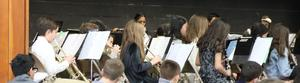 Photo of Tamaques band director Marisa Minogue conducting Grade 5 band in winter concert.
