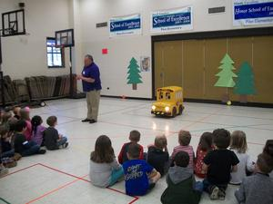 Buster the Bus visiting with kindergarten students in the gym.