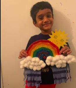 Boy holding rainbow, sun, and rain project