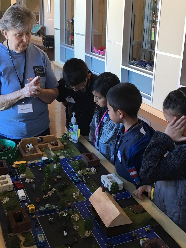 volunteer explains to students impact of having stray animals in neighborhood around mini model of city