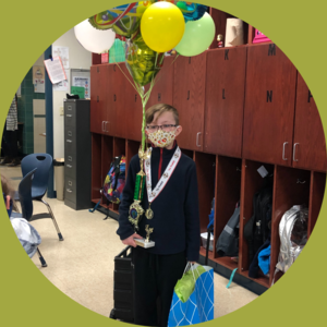 boy holding balloons & trophy