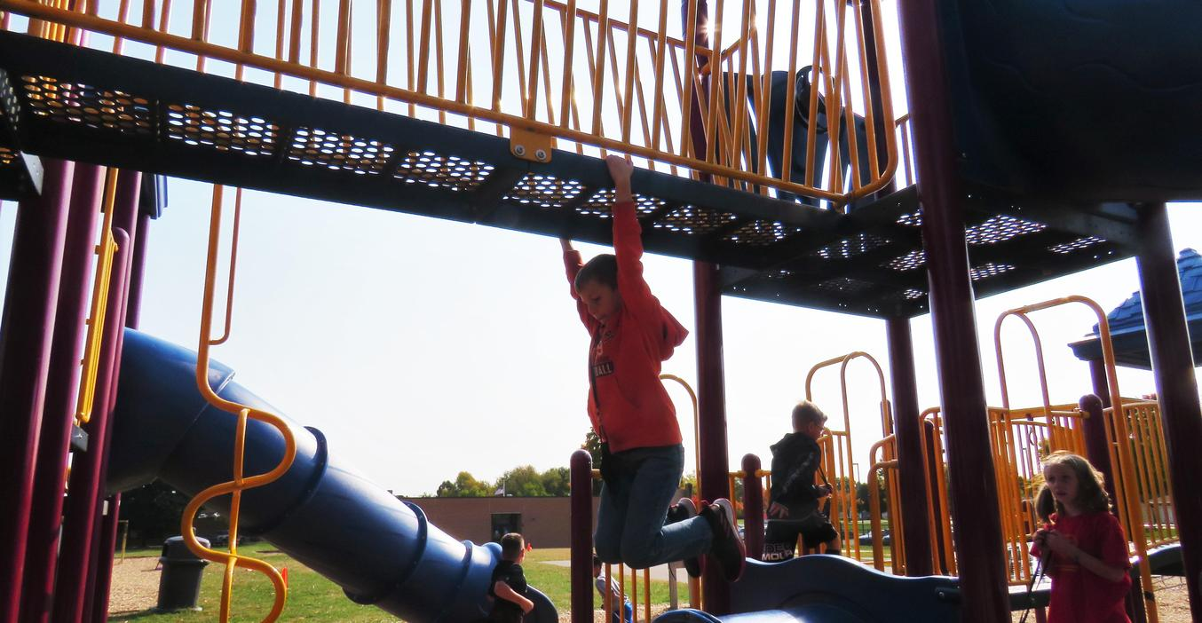 TK Students play on the play structure.
