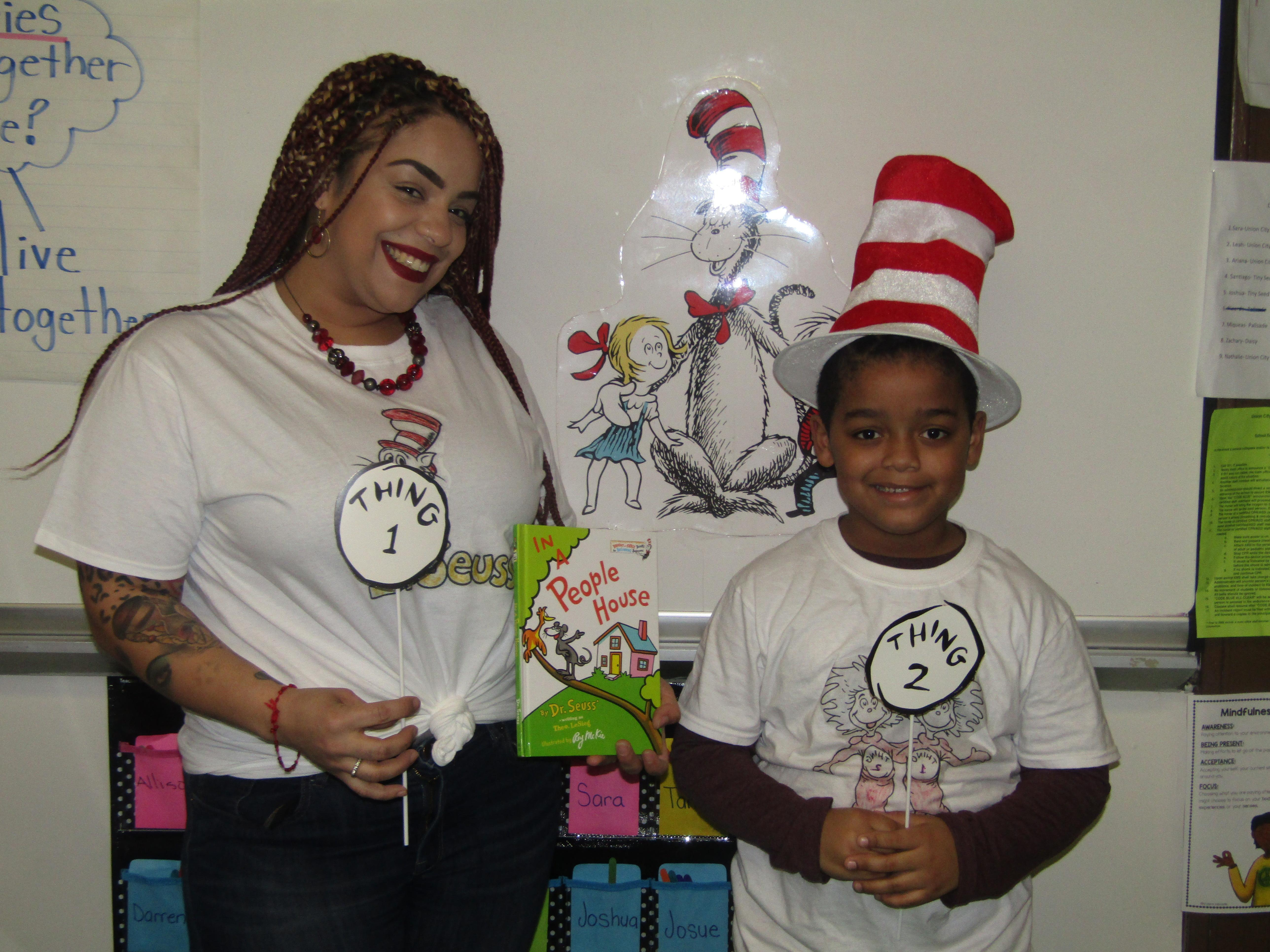 proud mom and son wearing matching things 1 & 2 shirts holding dr. seuss book