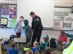 Officer Tom Goggins demonstrates with his son how he handcuffs someone.