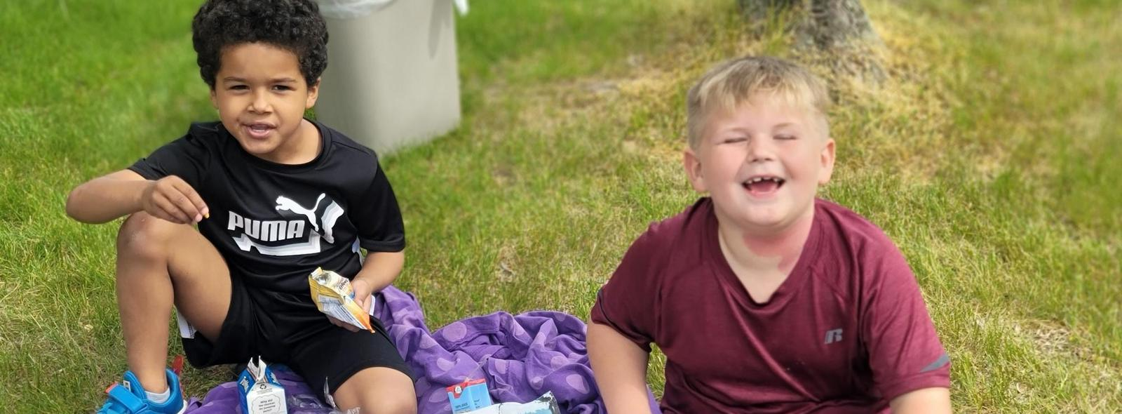 two kids eating lunch outside laughing