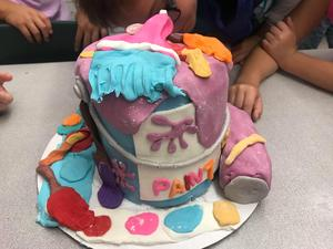 A paint can theme cake is full of color.