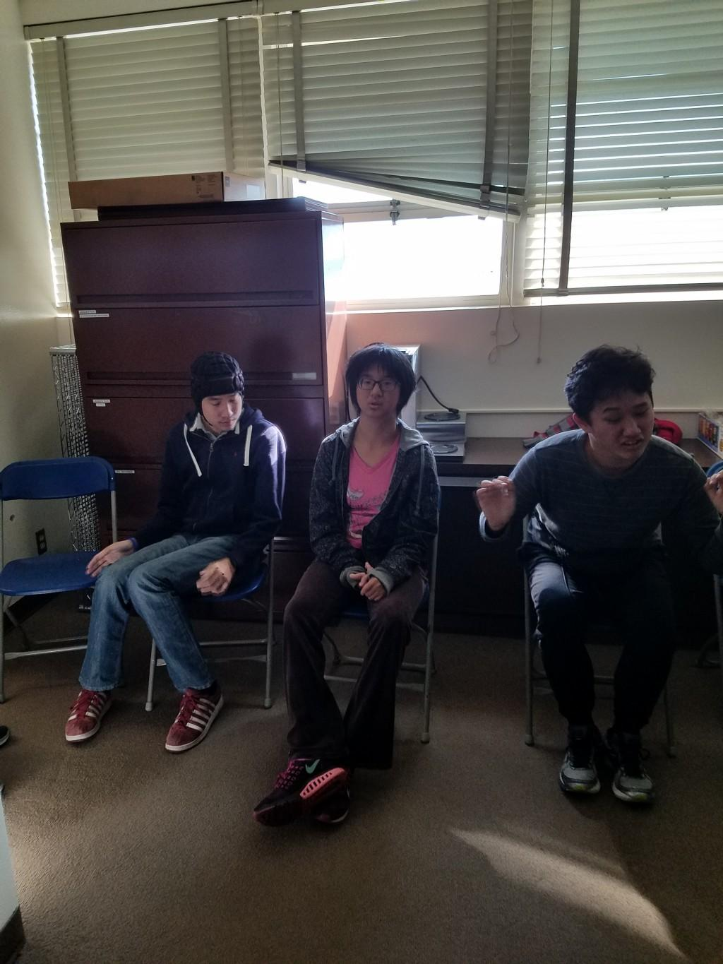 Three students sitting on chairs.