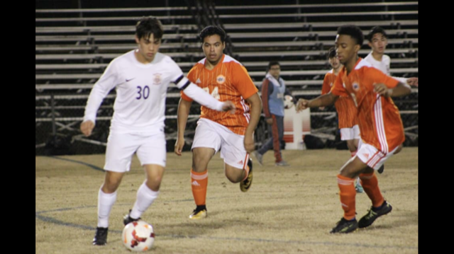 Rogelio Bermea an Davon Boast trying to take the soccer ball away from the other team member.