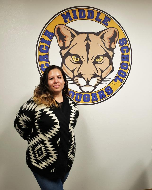 Alicia Alfaro standing in front of a wall with the Acacia logo on it.