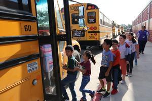 Escobar Rios Elementary students boarding the bus.