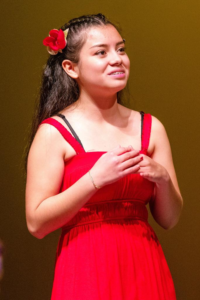 Kathy Santos, playing Little Ti Moune, crosses her hands across her chest and looks into the audience.