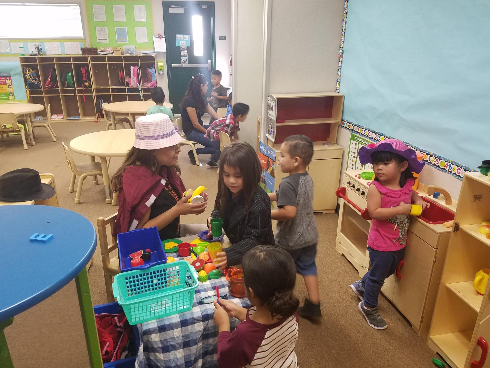 Students playing in dramatic play area with teacher