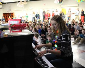 Music teacher Leigh Berkley accompanies the students in the holiday sing-a-long.