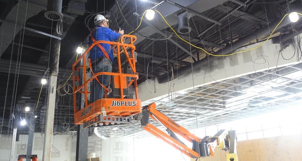 This snapshot shows a construction crew member installing ceiling mounted audio video system cables in the large group instruction room during the two days immediately prior to the Thanksgiving holiday recess period.