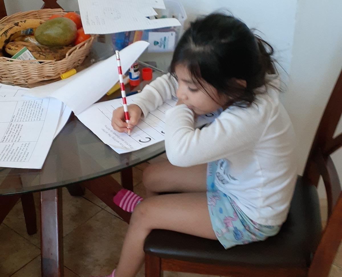 girl in her pj's doing her work
