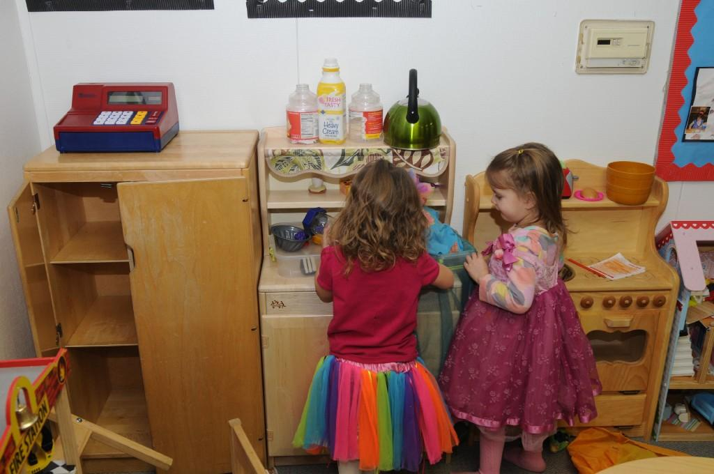 girls playing in a toy kitchen