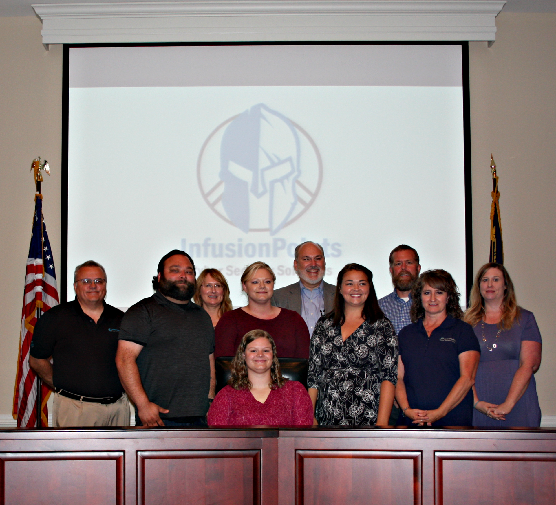 Kaitlyn Bell poses with her family in the Board Room during apprenticeship signing.
