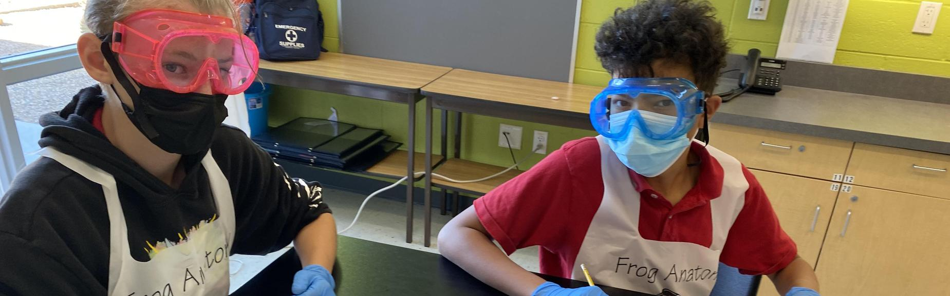 Two boys wearing masks and goggles working on a science experiment.