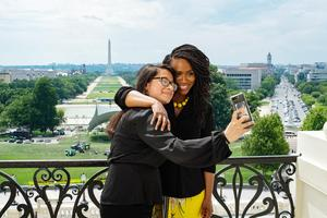 A student takes a selfie with Congresswoman Pressley with a view of the Washington Mall in the background